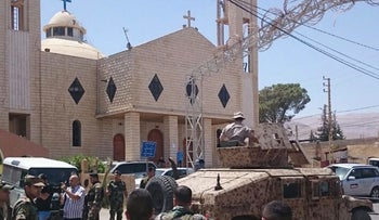 Lebanese army patrol in front a church in Qaa, a predominantly Lebanese Christian village only few hundred meters (yards) away from the Syrian border, eastern Lebanon, Monday, June 27, 2016.
