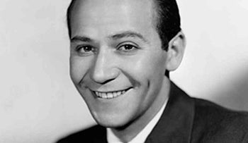"Frank Loesser: An aggressively lowbrow creative talent who was behind the smash hits ""Guys and Dolls,"" and ""How to Succeed in Business Without Really Trying"", among others: Shown here with impeccably combed hair, smiling, wearing white shirt, dark tie, darker suit, and a folded white kerchief in his jacket pocket."