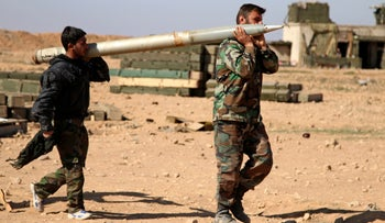 Soldiers from the Syrian army carry a rocket to fire at ISIS positions in the province of Raqqa, Syria, February 17, 2016.