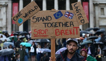 "A demonstrator holds up a placard saying ""Stand together Stop Brexit"" at an anti-Brexit protest in Trafalgar Square in central London on June 28, 2016."