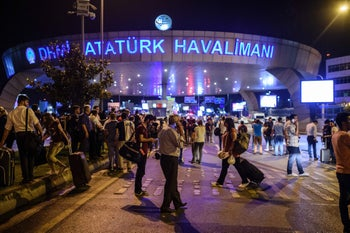 People stand outside the entrance as they leave the airport after two explosions hit the Turkey's biggest airport of Ataturk in Istanbul, on June 28, 2016.