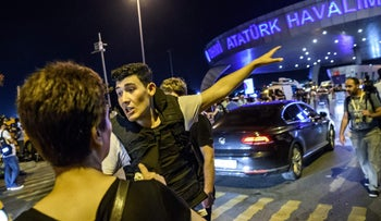 A Turkish police officer directs a passenger at Ataturk airport in Istanbul June 28, 2016 after two explosions followed by gunfire hit Turkey's biggest airport.