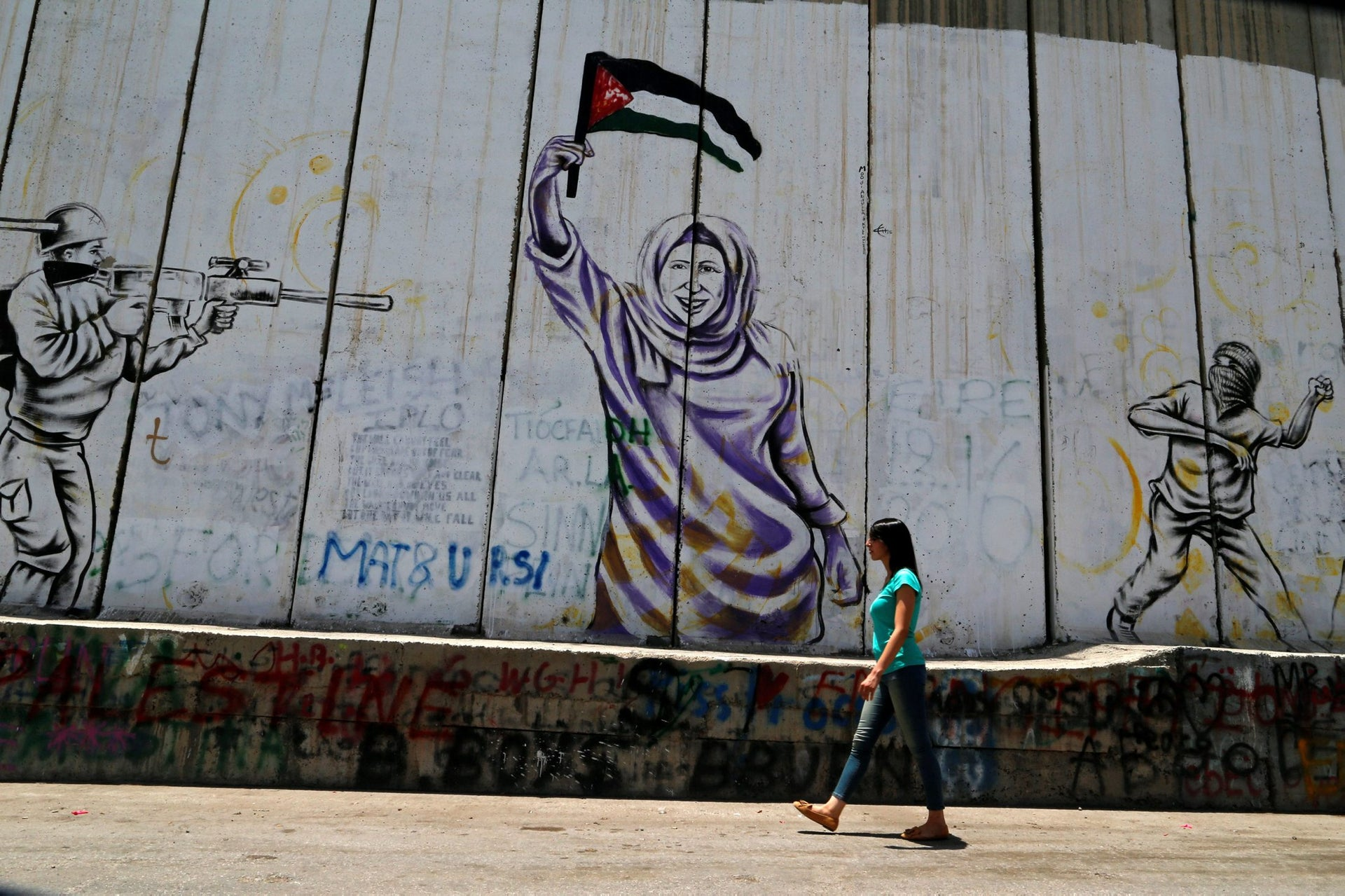 Palestinian swimmer Mary Al-Atrash, 22, who will represent Palestine at the 2016 Rio Olympics, walks past the Israeli barrier in the West Bank town of Bethlehem June 27, 2016.