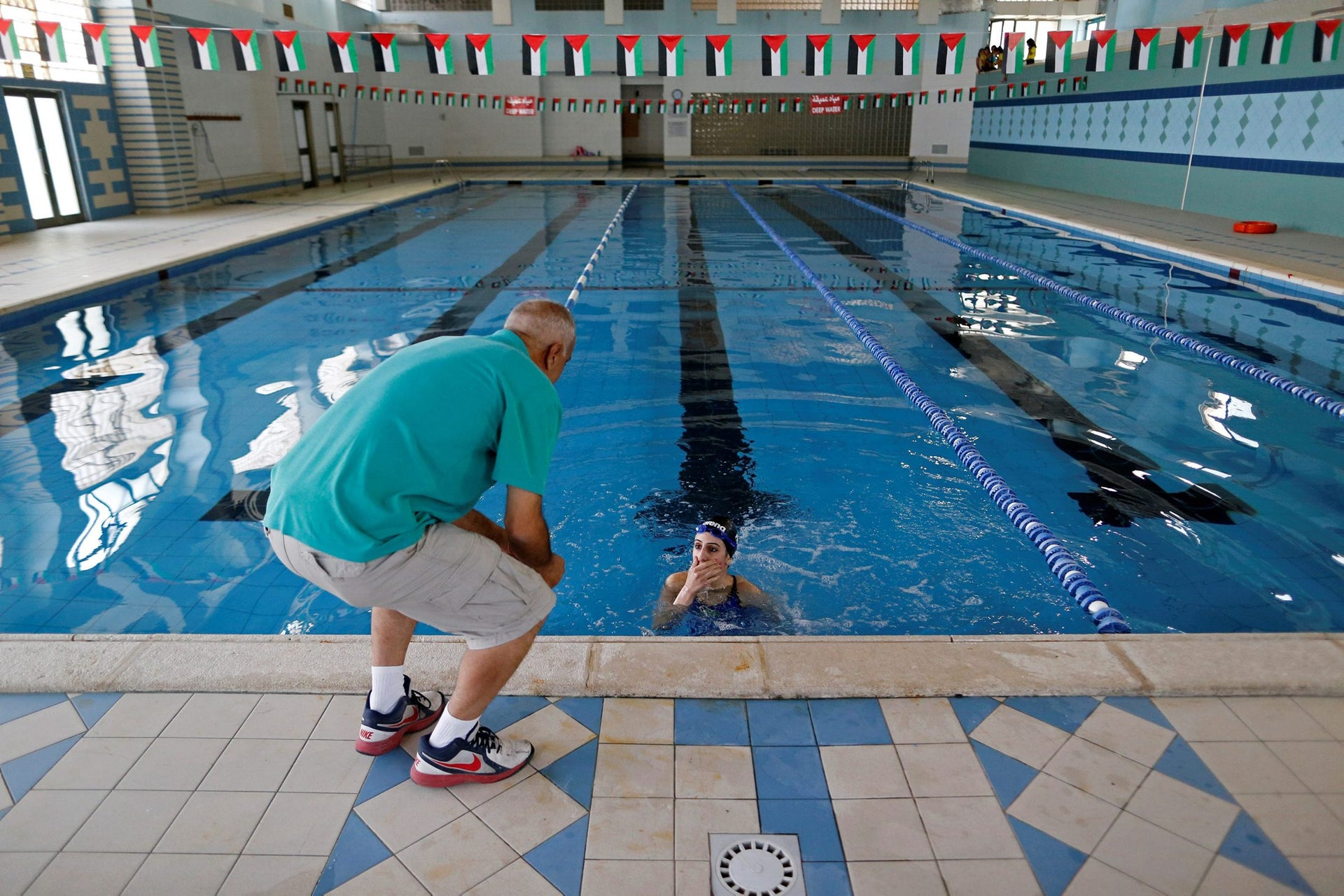 Palestinian swimmer Mary Al-Atrash, 22, who will represent Palestine at the 2016 Rio Olympics, speaks with her father as she trains in a swimming pool in Beit Sahour, near the West Bank town of Bethlehem, June 27, 2016.