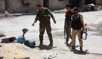 Syrian army soldiers check unexploded homemade rockets while patrolling government-controlled Aleppo's al-Khalidiya area where the army progressed toward al-Layramoun and Bani Zeid June 28, 2016.