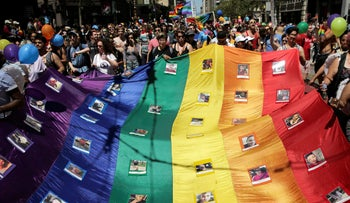 Marchers hold a rainbow flag with photos of the victims of the Orlando mass shooting during the San Francisco LGBT Pride Parade, San Francisco, California, U.S. June 26, 2016.