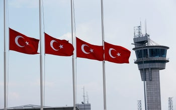 Turkish flags, with the control tower in the background, fly at half mast at the country's largest airport, Istanbul Ataturk, June 29, 2016.