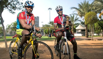 Michael Keflemarim (L) and Emanuel Gebremichel, on their bikes, with their medals and trophies.