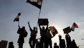 Supporters of Egypt's president Abdel-Fattah el-Sissi hold his poster and national flags as they celebrate the official announcement declaring him the next president at Tahrir Square in Cairo, Egypt, Friday, June 6, 2014.