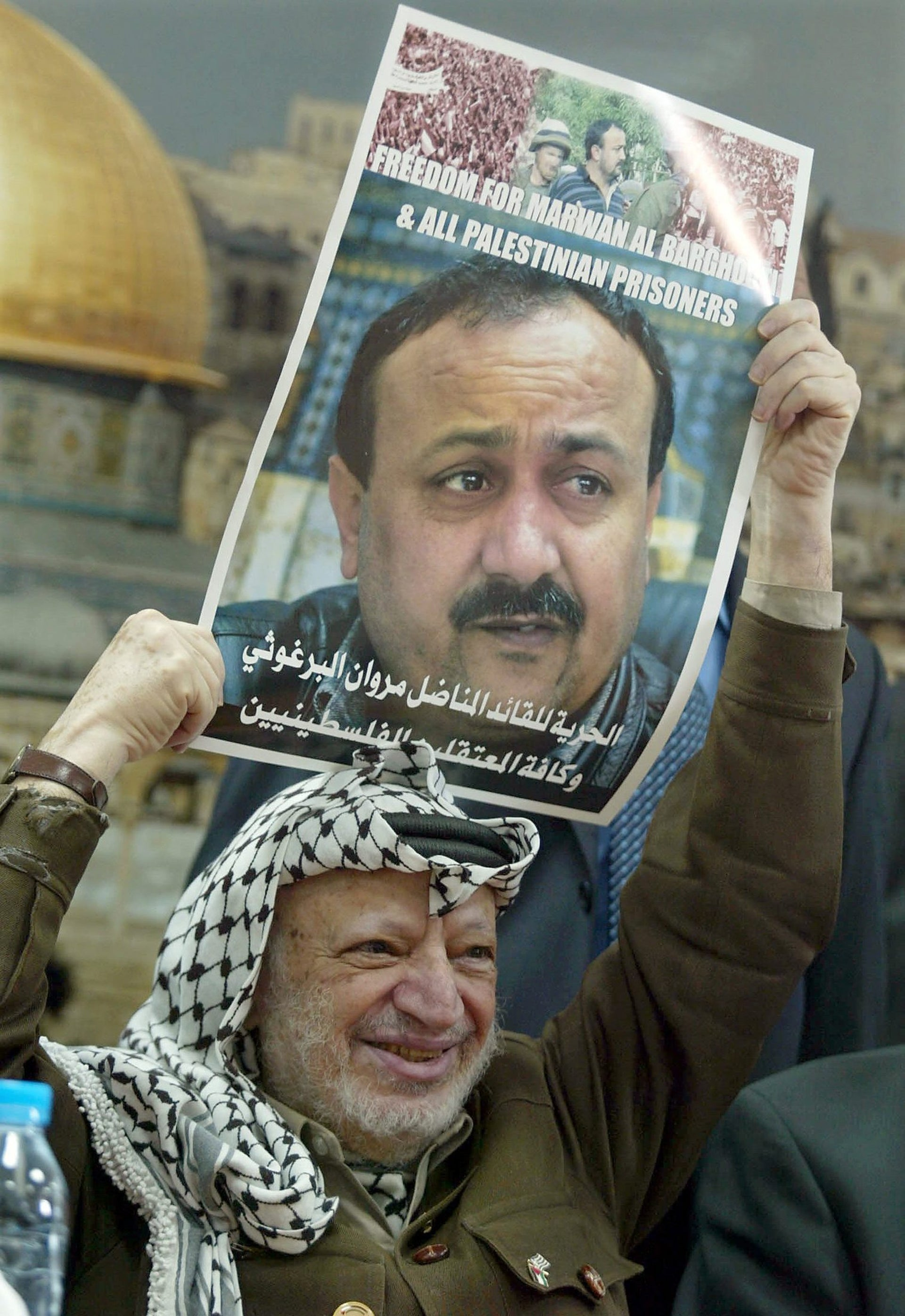 Palestinian leader Yasser Arafat holds a poster of jailed leader of the Fatah movement in the West Bank Marwan Barghouti during a ceremony in his office in of Ramallah, February 12, 2004.