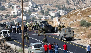 Israeli soldiers secure the scene of a shooting attack near Hebron, West Bank, Friday, July 1, 2016.