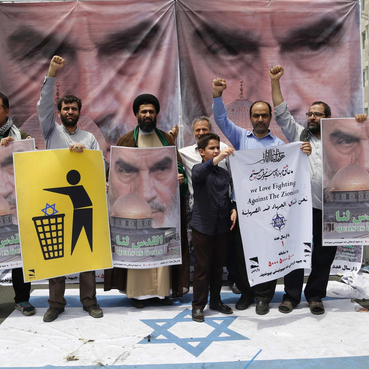 Iranian protestors hold anti-Israeli placards with portraits of late revolutionary leader Ayatollah Ruhollah Khomeini during a parade marking al-Quds (Jerusalem) Day in Tehran on July 01, 2016.