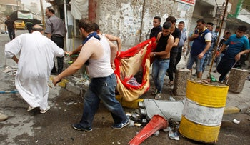 Civilians carry the body of a victim killed in a suicide car bomb in the Karrada shopping area, in Baghdad, Iraq, July 3, 2016.