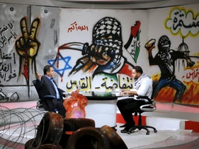 Palestinian presenter Raji Al-Hams (R) listens to Hamas official Salah al-Bardweel at the studio of Hamas-run Al-Aqsa TV in Gaza City, October 27, 2015