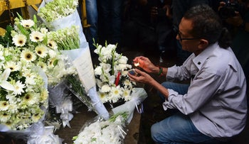 A Bangladeshi man lights a candle on floral arrangement near the Holey Artisan Bakery, the scene of a fatal attack and siege, Dhaka, Bangladesh, July 3, 2016.
