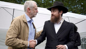 Labour Party leader Jeremy Corbyn shakes hands with Rabbi Mendy Korer at an anti-racism rally in London, July 2, 2016.