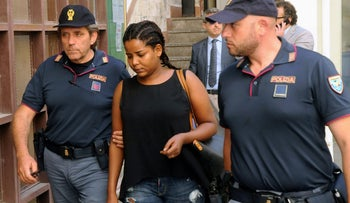 A woman is escorted by Italian police officers after they arrested people, who they said, belonged to an organisation that had smuggled thousands of migrants into Europe from Africa, in Palermo, Italy July 4, 2016.