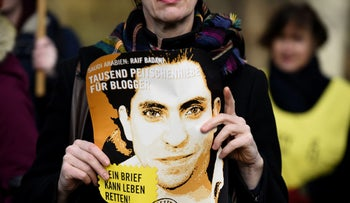 An Amnesty International activist holds a picture of Saudi blogger Raif Badawi during a protest against his flogging punishment in front of Saudi Arabia's embassy in Berlin, January 29, 2015.