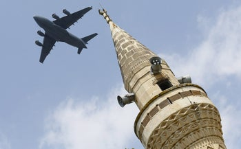 A U.S. Air Force Boeing C-17A Globemaster III large transport aircraft flies over a minaret after taking off from Incirlik air base in Adana, Turkey, August 12, 2015.