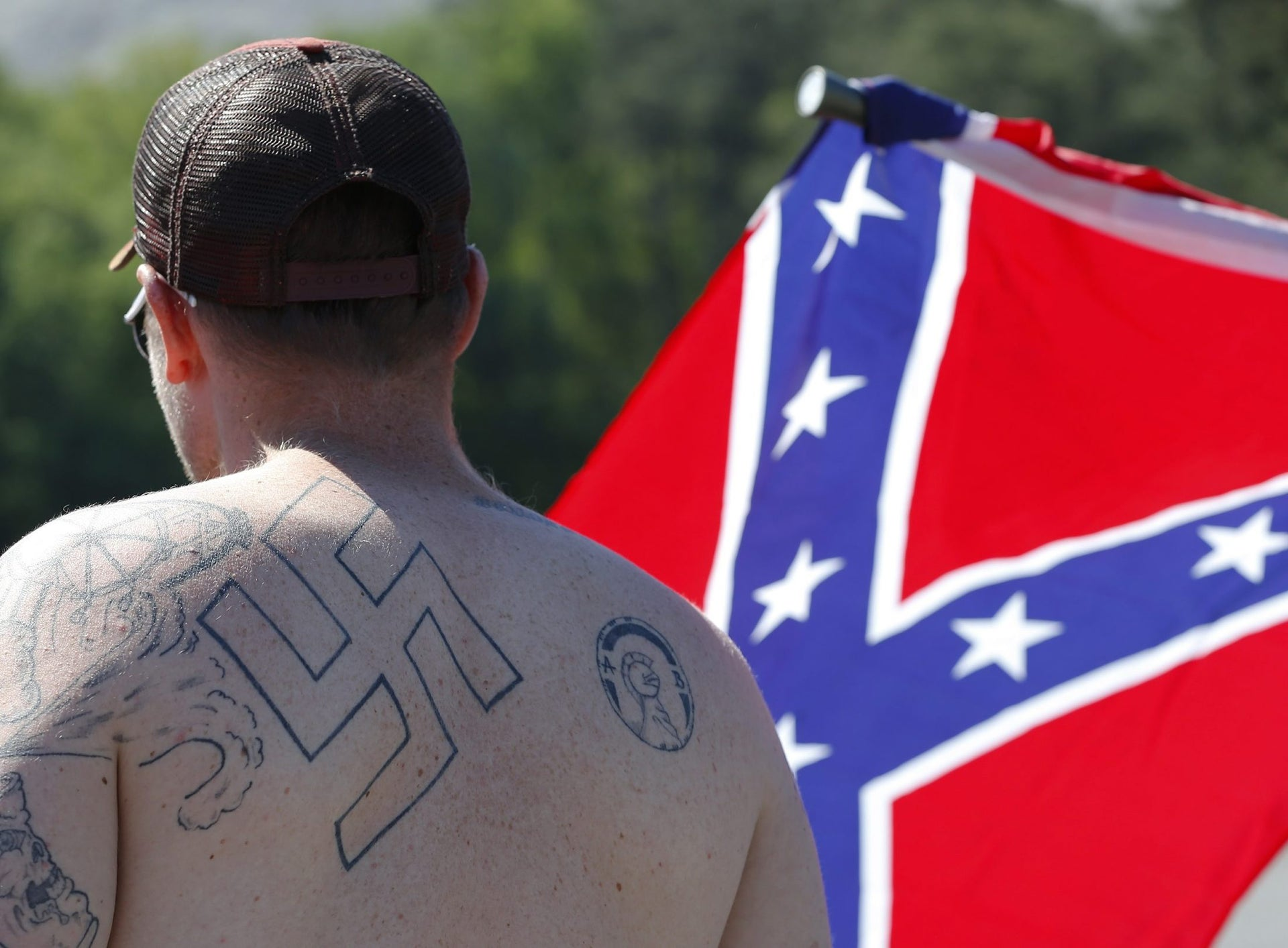 ADVANCE FOR JUNE 30 -In this April 23, 2016 photo, a man walks during a protest at Stone Mountain Park, in Stone Mountain, Ga. The Ku Klux Klan is trying to raise its hooded head 150 years after it was founded following the Civil War. The ease of online communication is helping the infamous white separatist movement reach new members, and issues important to the Klan like opposition to immigration are coming to the political forefront as the presidential election looms.
