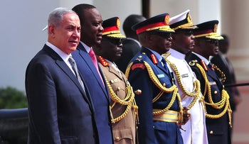 Prime Minister Benjamin Netanyahu (L), flanked by Kenya's President Uhuru Kenyatta (2nd L) and military officials, during his visit to State House in Nairobi on July 5, 2016, during his trip with Africa.