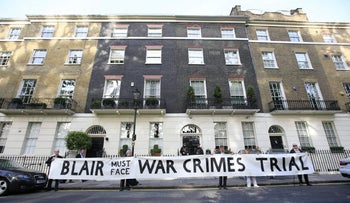 Protesters hold a banner outside the London home of former Prime Minister Tony Blair ahead of the publication of the Chilcot report into the Iraq war in London, Wednesday, July 6, 2016.