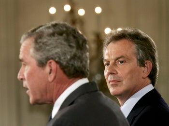 In this 2005 photo, then British Prime Minister Tony Blair, right, looks at then U.S. President George W. Bush at a joint news conference in the East Room of the White House in Washington June 7.
