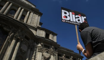 A demonstrator holds a placard during a protest near the venue of the publication of the Iraq Inquiry report in London on July 6, 2016.