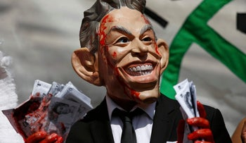 A demonstrator wearing a mask to impersonate Tony Blair holds bundles of fake money during a protest before the release of the John Chilcot report into the Iraq war, in London, Britain July 6, 2016.