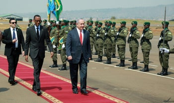 Israeli Prime Minister Benjamin Netanyahu (C) walks alongside Rwandan President Paul Kagame as he inspects a guard of honor upon arriving at the airport in Kigali, Rwanda, July 6, 2016.