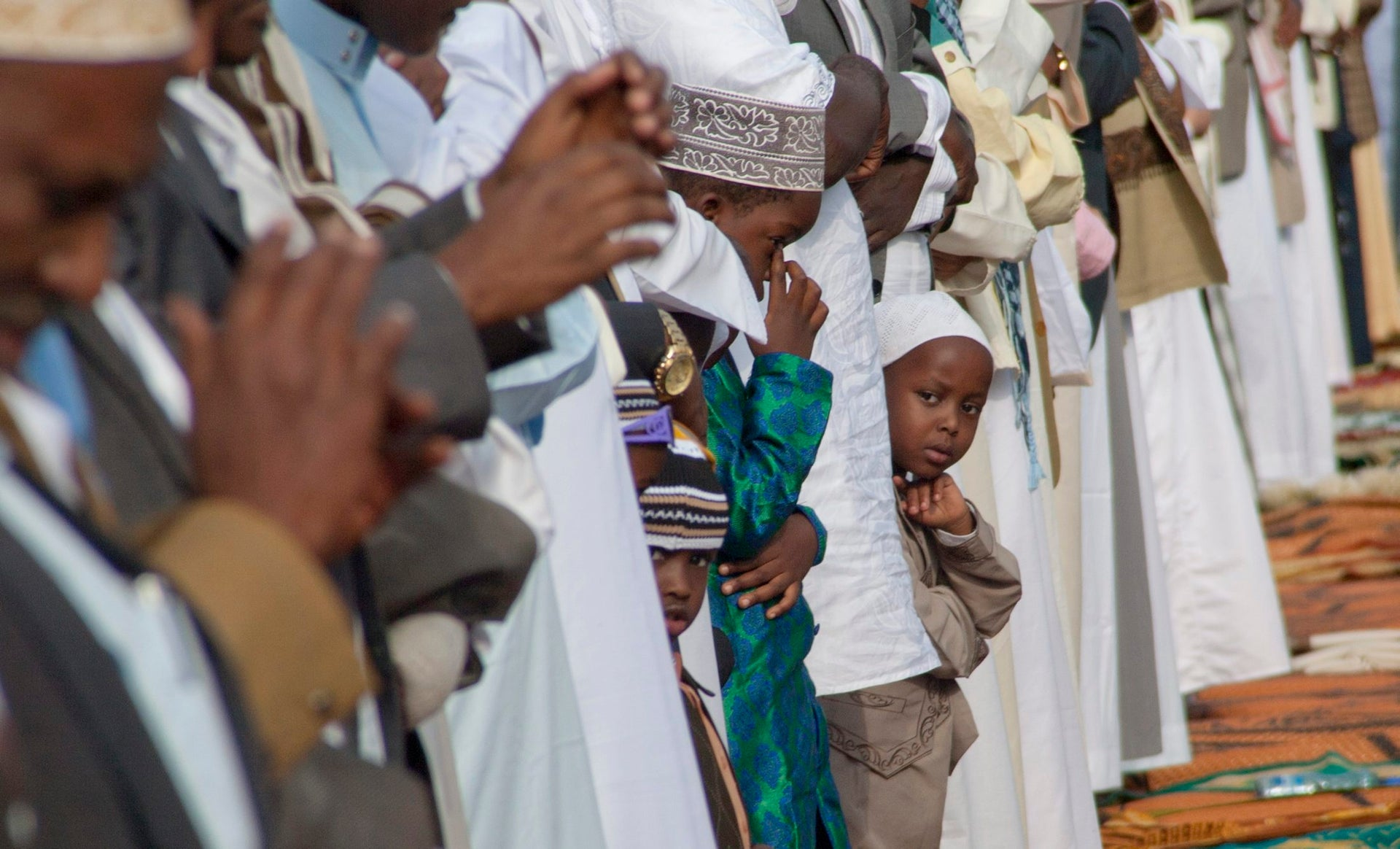 Kenyan Muslim boys join in prayers during the Id al-Fitr on the open ground in Nairobi, Kenya, Wednesday, July 6, 2016.