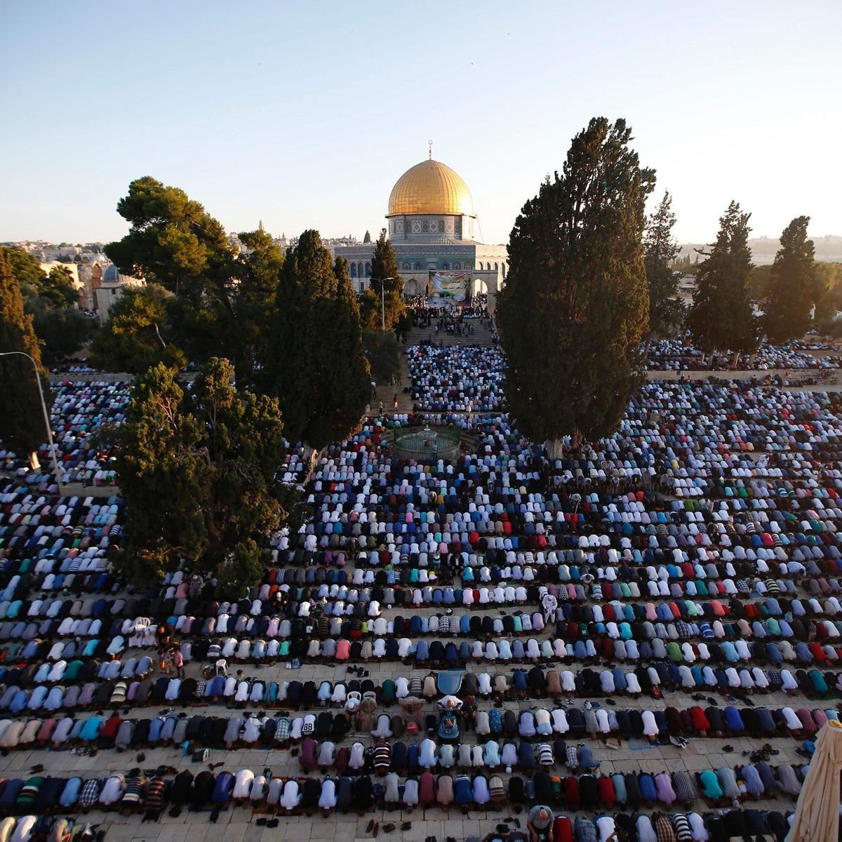 Palestinian Muslim men perform the morning Id al-Fitr prayer near the Dome of Rock at the Al-Aqsa Mosque compound in the Old City of Jerusalem on July 6, 2016.