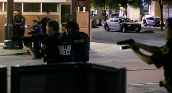 Dallas police move to detain a driver after several police officers were shot in downtown Dallas, Thursday, July 7, 2016.