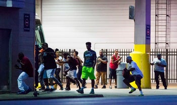 Bystanders run for cover after shots fired at a Black Live Matter rally in downtown Dallas on July 7, 2016.