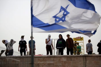 Israeli settlers stand on the roof of a synagogue in the West Bank settlement of Givat Zeev, north of Jerusalem on November 4, 2015.