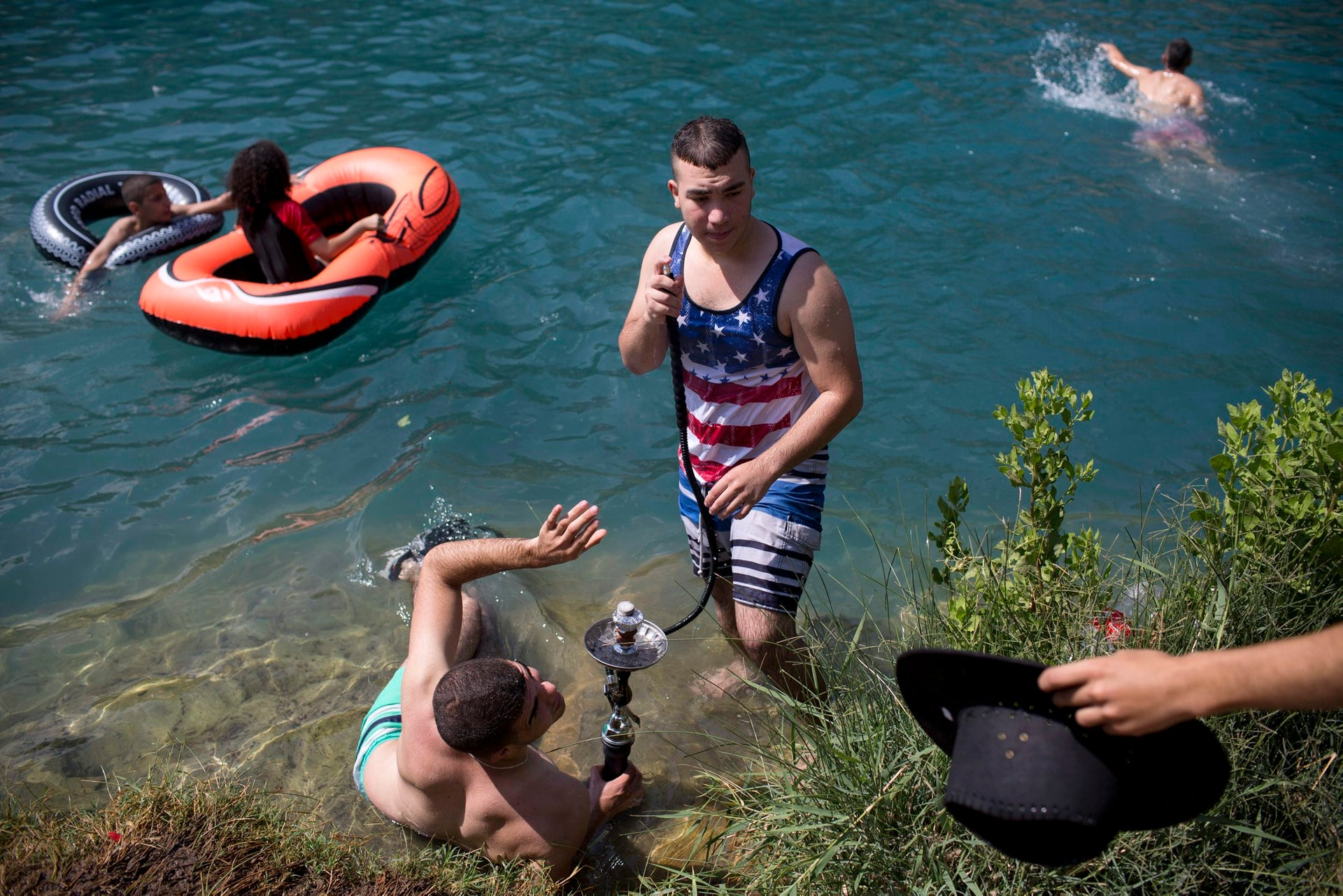 Israeli Arabs cool off in a spring as they celebrate the Eid al-Fitr holiday at the Gan HaShlosha national park near the northern Israeli Town of Beit Shean, Friday, July 8, 2016. Eid al-Fitr marks the end of the Muslim holy fasting month of Ramadan.