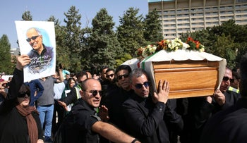 Iranian film assistant directors carry Kiarostami's coffin while a woman holds a poster of his face at his funeral ceremony in Iran July 10, 2016.