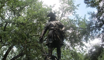 Statue of James Oglethorpe, founder of Savannah, in Chippewa Square, completed in 1910 by Daniel Chester French. The picture shows the statue of the man leaning on his sword with his right hand, on a pedestal, shining in the sun and surrounded by trees,