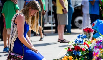 Sarah Preibisius, wife of Dallas Police Officer Justin Preibisius, kneels next to a memorial in honor of fallen police officers, July 10, 2016 outside Dallas Police headquarters.