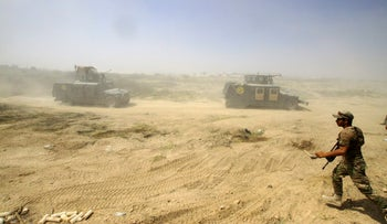 Iraqi security forces advance their positions during the fight against ISIS militants in Fallujah, Iraq, June 15, 2016.