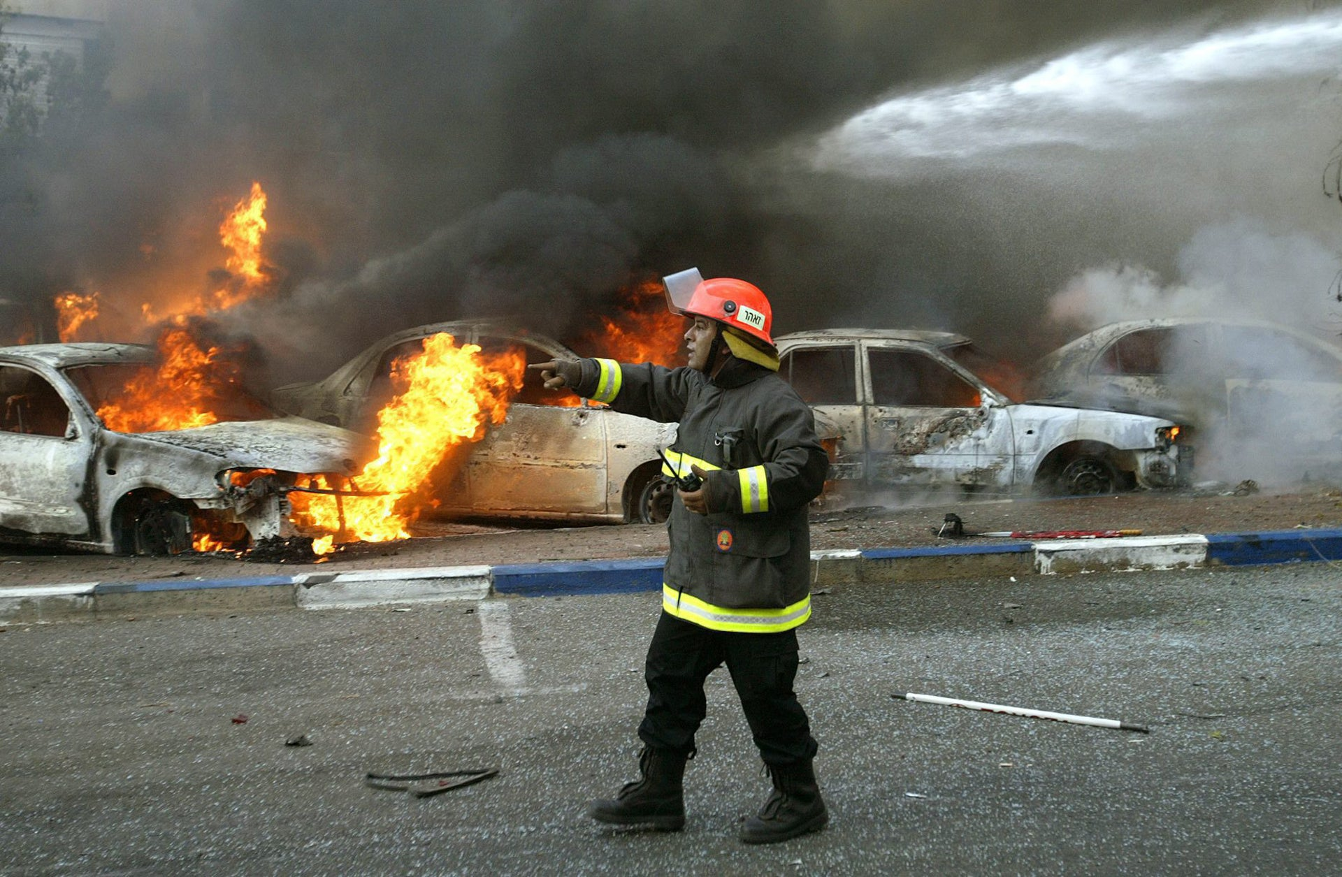 Israeli firefighters arrive to extinguish a fire at the scene of a Hezbollah rocket attack in the northern Israel city of Haifa, Aug. 13, 2006.