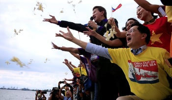 Protesters throw flowers and chant anti-Chinese slogans during a rally July 12, 2016 over the South China Sea disputes. A man (front) wears a shirt 'China out of West PHL Sea.'