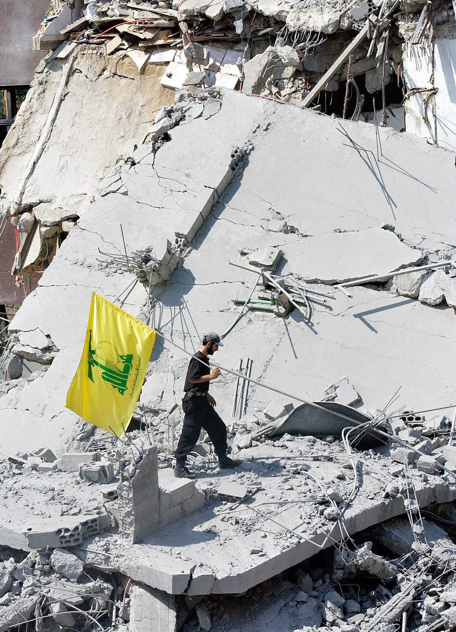 A Lebanese member of the Hezbollah militant group poses for the media with his group's yellow flag on the rubble of a destroyed apartment building, in the village of Jbaa, east of the port city of Sidon, southern Lebanon, Saturday, July 29, 2006, after it was hit by Israeli airstrikes overnight. Israeli troops and Hezbollah guerrillas traded heavy bombardment and gunfire Saturday around a Lebanese border town that Israel has tried to capture for the past week, facing tough and bloody resistance. Warplanes blasted bridges, flying some 120 missions in the past day and a half.
