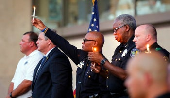 Dallas Police Chief David Brown, center, holds a lit candle up during a ceremony in front of City Hall to honor fallen officers, July 11, 2016 in Dallas.