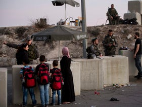 Israeli border police check Palestinians' identification cards at a checkpoint as they exit the Arab neighborhood of Issawiyeh in Jerusalem, October 22, 2015.