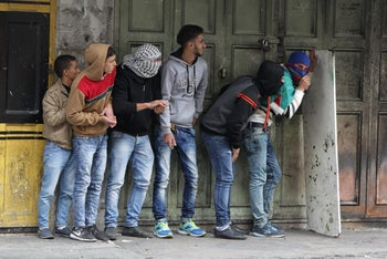 In Hebron, Palestinian stone-throwers hide behind a board during clashes with Israeli security forces. November 10, 2015.