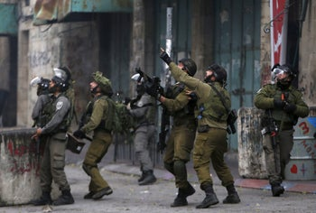 Israeli security forces react during clashes with Palestinian demonstrators in Hebron. November 10, 2015.