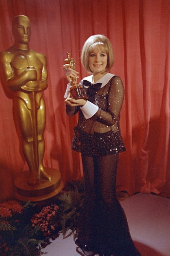 """In this April 14, 1969 file photo, actress and singer Barbra Streisand wears a sequined Arnold Scaasi bell-bottomed sheer pantsuit as she poses with her Oscar for her role in """"Funny Girl."""""""