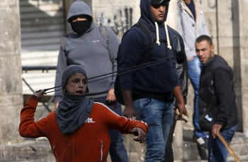 A Palestinian boy uses a sling to hurl stones towards Israeli troops during clashes in the West Bank city of Hebron October 29, 2015.