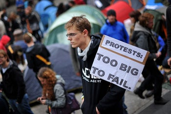 A protester holds a placard that says 'Protests: Too big to fail' outside St. Paul's Cathedral in the city of London on October 16, 2011 as part of a global day of protests inspired by the 'Occupy Wall Street' movement.